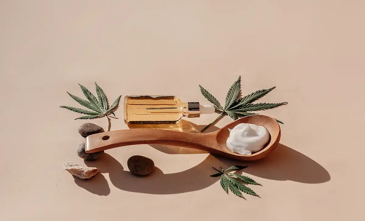Wooden spoon with white cream, around the spoon are three cannabis leaves, a few stones and a bottle with pipette